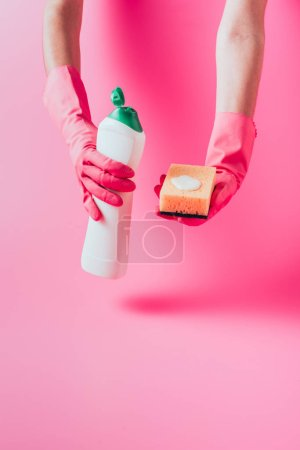 Photo for Cropped image of female cleaner in rubber gloves holding washing sponge and cleaning fluid - Royalty Free Image