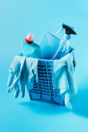 close up view of bucket with washing powder, cleaning fluids, rubber gloves and rag on blue background