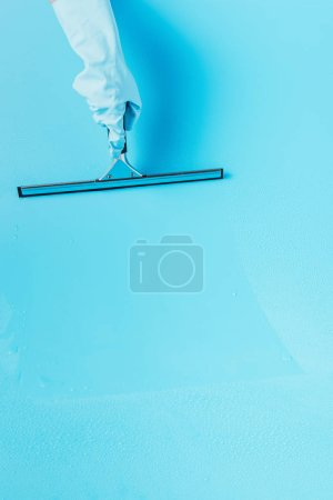 cropped image of woman in rubber glove cleaning floor by squeegee, blue background