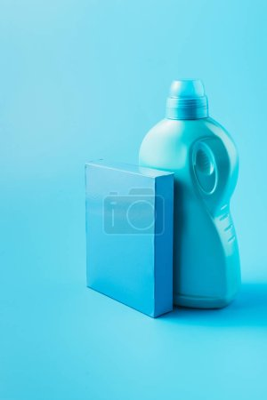 close up view of washing powder and laundry liquid, blue background
