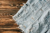 top view of light denim textile on wooden table