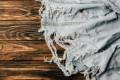 top view of light denim textile on wooden surface