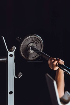 cropped image of female bodybuilder doing exercise with barbell at gym, black background