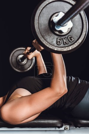 cropped image of sportswoman exercising with barbell at gym, black background