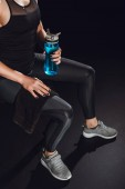 cropped image of sportswoman resting with towel and sport bottle of water at gym, black background