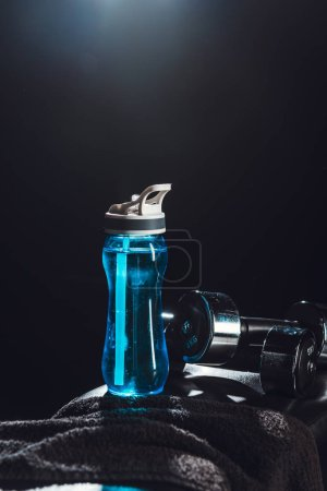 Photo for Close up view of sport bottle, towel, dumbbells at gym, black background - Royalty Free Image