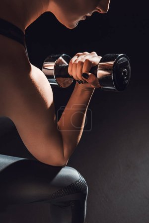 cropped image of female athlete exercising with dumbbell at gym, black background