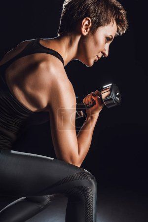 Photo for Side view of female athlete exercising with dumbbell at gym, black background - Royalty Free Image