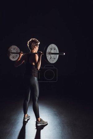vue arrière du jeune athlète féminine travailler avec fond barbell, noir