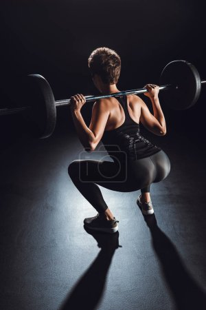 Photo for Rear view of sportswoman exercising with barbell, black background - Royalty Free Image