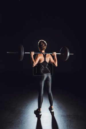 rear view of sportswoman exercising with barbell, black background