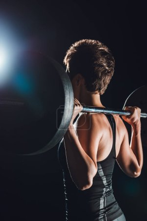 side view of sportswoman exercising with barbell, black background
