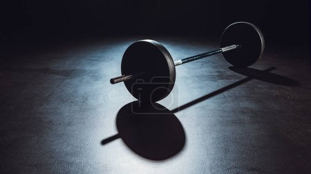 Photo for Close up view of barbell on floor with shadow at gym, black background - Royalty Free Image