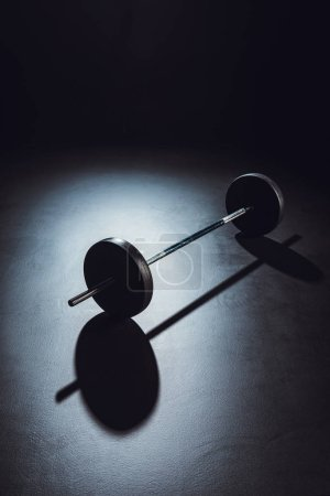selective focus of barbell on floor with shadow at gym, black background