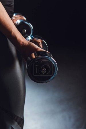 partial view of sportswoman working out with dumbbells, black background