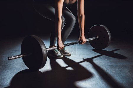 Photo for Cropped image of female athlete working out with barbell, black background - Royalty Free Image