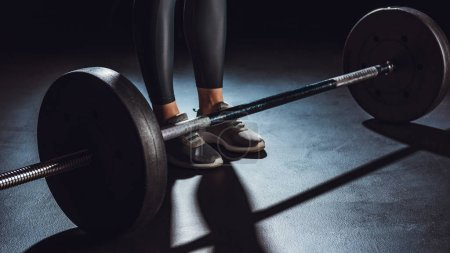 Photo for Partial view of sportswoman standing near barbell on floor at gym, black background - Royalty Free Image