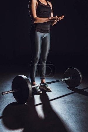 cropped image of female bodybuilder spreading chalk powder near barbell on floor at gym, black background