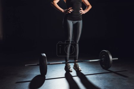 cropped image of female athlete standing with hands on waist near barbell on floor at gym, black background