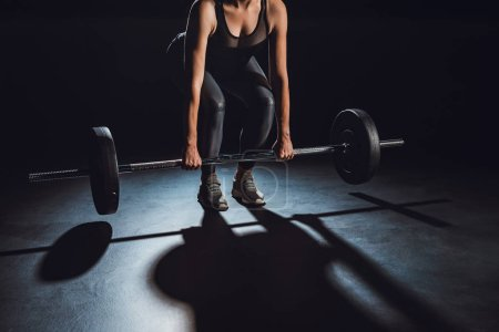 Photo for Partial view of sportswoman exercising with barbell at gym, black background - Royalty Free Image
