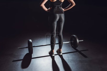 cropped image of sportswoman standing with hands on waist near barbell on floor at gym, black background