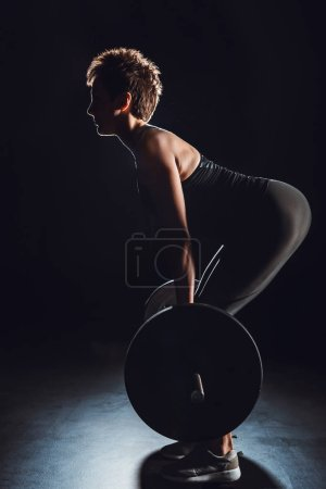 side view of female athlete doing exercise with barbell at gym, black background