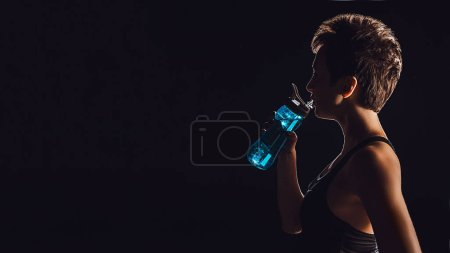 side view of sportswoman drinking water from bottle, black background