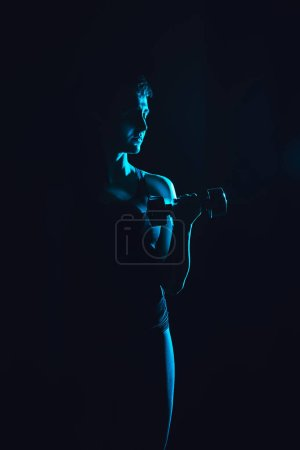 Photo for Toned picture of sportswoman working out with dumbbell, black background - Royalty Free Image