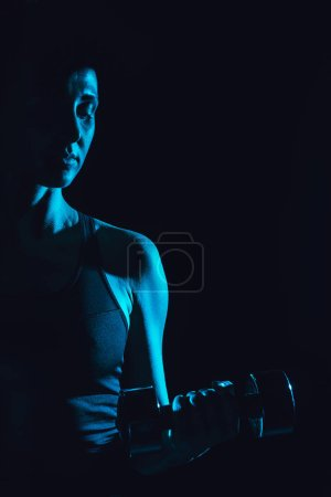 toned picture of female athlete exercising with dumbbell, black background