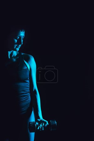 toned picture of sportswoman working out with dumbbell, black background