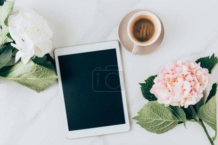 Photo pour Vue de dessus des fleurs d'hortensia, de café et d'une tablette numérique avec écran blanc sur la surface du marbre - image libre de droit