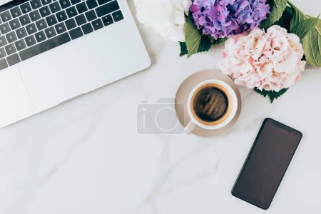 flat lay with coffee, laptop, smartphone and hortensia flowers on marble surface