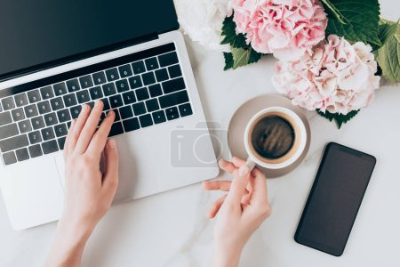 cropped view of woman using laptop and holding cup of coffee on tabletop with smartphone and hortensia flowers