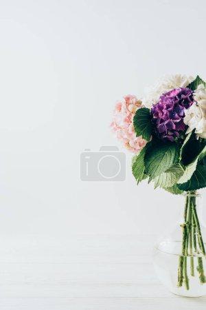 Foto de Coloridas flores de Hortensia en florero de cristal, en blanco - Imagen libre de derechos