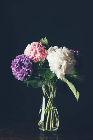 pink, white and purple hortensia flowers in glass vase, on black
