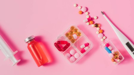 top view of different medicines and electric thermometer on pink surface