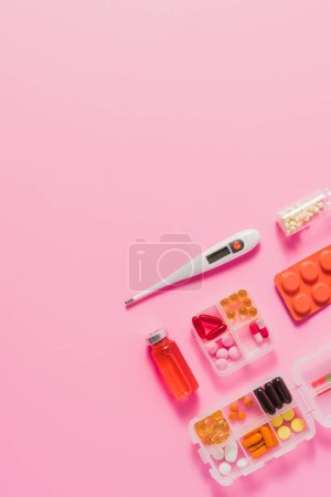 top view of different medicines and electric thermometer on pink