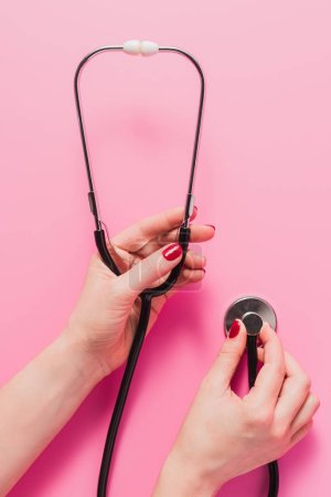 cropped shot of woman holding stethoscope on pink