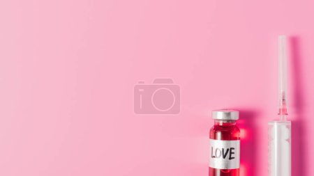 top view of syringe and bottle with love vaccine sign on pink tabletop