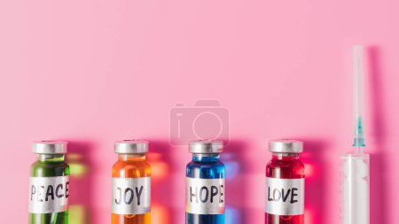 top view of syringe and bottles with love, hope, joy and peace vaccine signs in row on pink surface