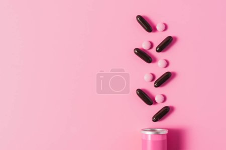 top view of can with arranged pink and black pills on pink