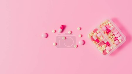 Photo for Top view of plastic case with various pills on pink - Royalty Free Image