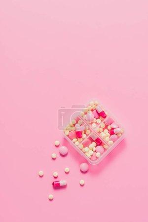 Photo pour Vue de dessus d'un récipient en plastique avec des pilules diverses sur rose - image libre de droit