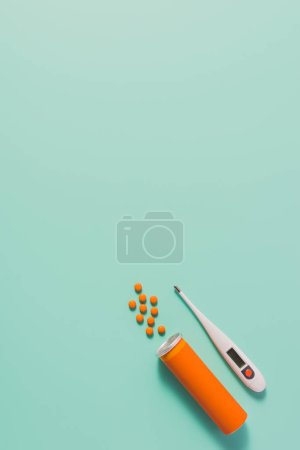top view of container with spilled medicines and electric thermometer on blue