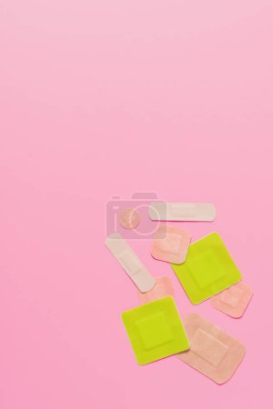 top view of various adhesive bandages on pink tabletop