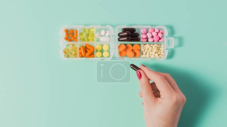 cropped shot of woman taking capsule from plastic case with various sorted pills on blue