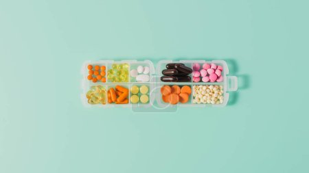 Photo for Top view of plastic case with various sorted pills on blue - Royalty Free Image