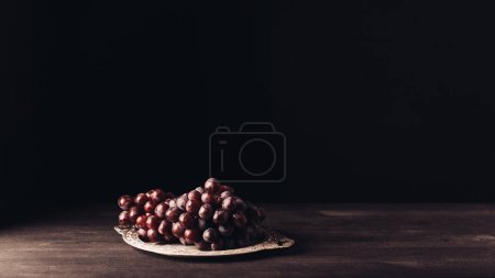 fresh ripe red grapes on vintage plate on wooden table on black