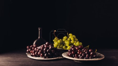 fresh ripe grapes on vintage plates and bottle of wine on wooden table on black