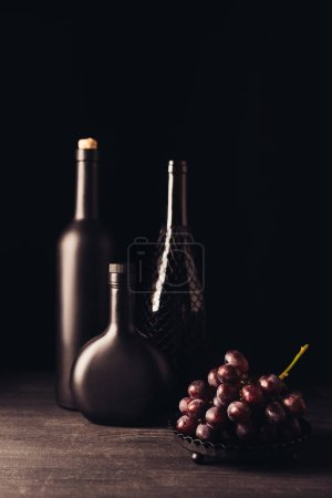 close-up view of fresh ripe red grapes and bottles of wine on wooden table on black
